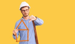 Handsome young man with bear wearing architect hardhat holding build project with angry face, negative sign showing dislike with thumbs down, rejection concept