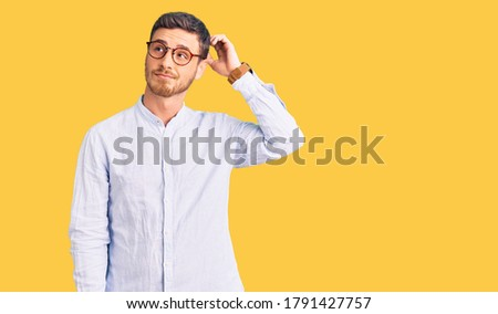 Handsome young man with bear wearing elegant business shirt and glasses confuse and wondering about question. uncertain with doubt, thinking with hand on head. pensive concept.  Foto stock ©