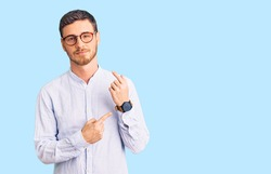 Handsome young man with bear wearing elegant business shirt and glasses in hurry pointing to watch time, impatience, looking at the camera with relaxed expression