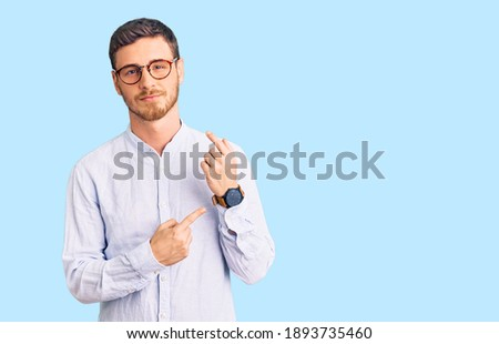 Handsome young man with bear wearing elegant business shirt and glasses in hurry pointing to watch time, impatience, looking at the camera with relaxed expression  Сток-фото ©