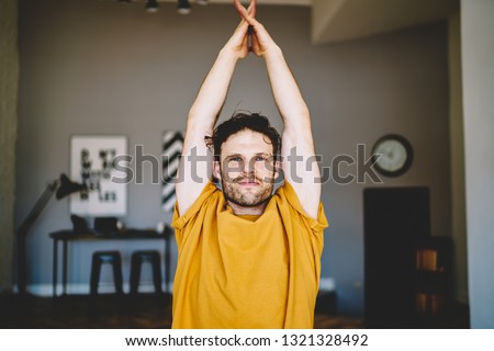 Handsome young man with blue eyes holding hands in namaste above the head above the head during meditation and relaxation in modern apartment.Motivated hipster guy doing yoga exercises during training #1321328492