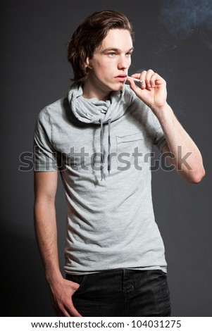 Handsome young man with brown long hair wearing grey shirt isolated on grey background. Smoking cigarette. Fashion studio shot. Expressive face.