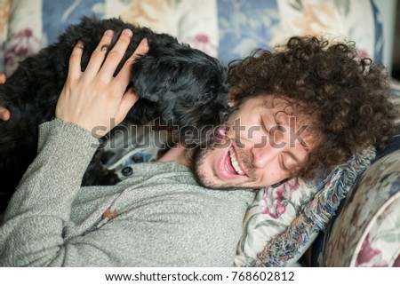 Handsome young man with curly brown hair laying on the couch laughing as his cute black dog is licking his face lovingly.