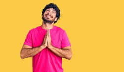 Handsome young man with curly hair and bear wearing casual pink tshirt begging and praying with hands together with hope expression on face very emotional and worried. begging.