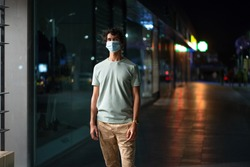 Handsome young man with face mask walks on city street at night