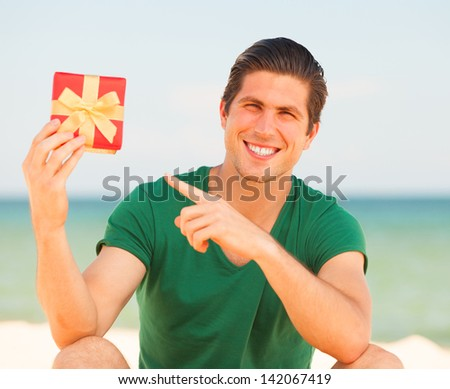 Handsome young man with gift at beach background