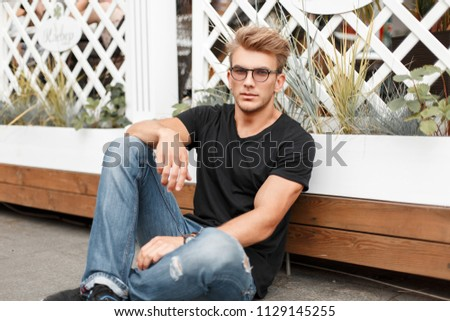 handsome young man with glasses in a fashionable black T-shirt sits near a wooden white fence #1129145255