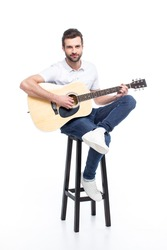Handsome young man with guitar sitting on bar stool isolated on white