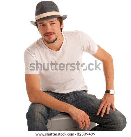 Handsome young man with hat rests on suitcase