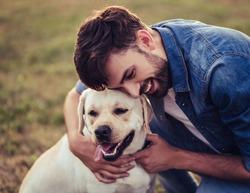 Handsome young man with labrador outdoors. Man on a green grass with dog labrador retriever.