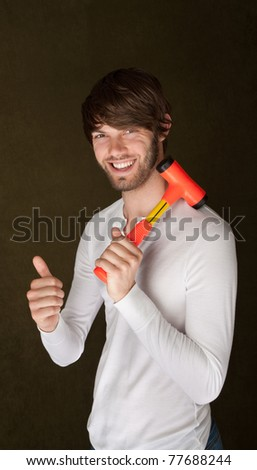 Handsome young man with mallet over his shoulder gives thumbs up