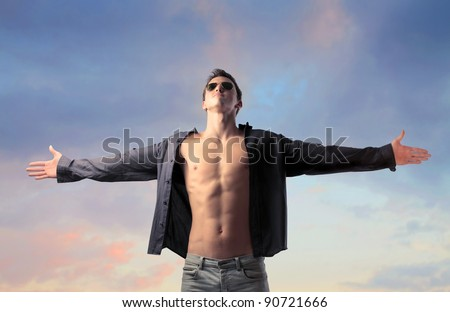 Handsome young man with open shirt stretching out his arms