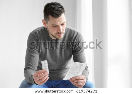 Handsome young man with pills and instruction at home