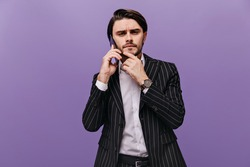 Handsome young man with stylish hairstyle, white shirt and black striped suit, looking straight forward, talking on phone and thinking about something. Brunette posing isolated over violet background
