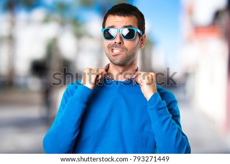 Handsome young man with sunglasses on unfocused background #793271449