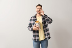 Handsome young man with tasty potato chips on light background