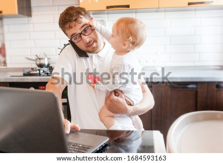 Photo of  Handsome young man working at home with a laptop with a baby on his hands. Stay home concept. Home office with kids.