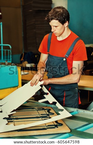 Handsome young man working in manufacture with boxes at factory for the production of cardboard packaging