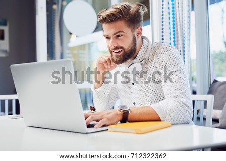 Handsome young man working on laptop while sitting in modern cafeteria