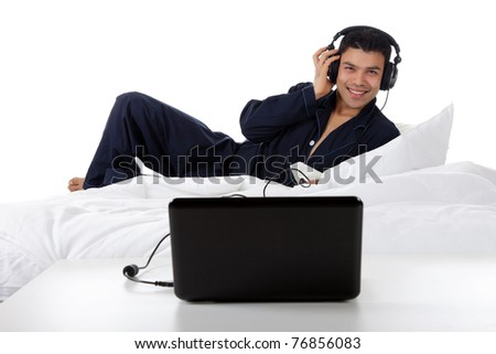 Handsome young nepalese man in pajamas with headphones and laptop, relaxing in bed and listening music from the internet. Focus on laptop. Studio shot. White background.