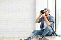 Handsome young photographer sitting on window sill
