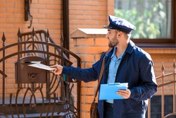 Handsome young postman putting letter in mail box outdoors