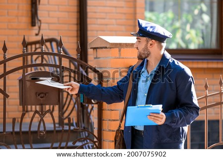 Handsome young postman putting letter in mail box outdoors Stockfoto ©