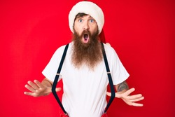 Handsome young red head man with long beard wearing santa claus costume with suspenders afraid and shocked with surprise and amazed expression, fear and excited face.