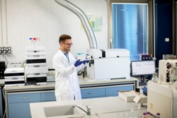 Handsome young researcher workin with chemical samples in laboratory with HPLC system and  chromatography equipment