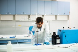Handsome young researcher working with blue liquid at separatory funnel in the laboratory