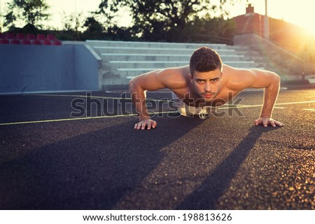 Handsome young shirtless Caucasian fitness man doing push-ups outdoors on sunny summer day. Back lit horizontal image.