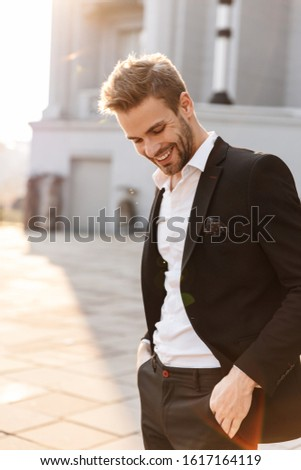 Handsome young smiling businessman standing at the city street, wearing suit