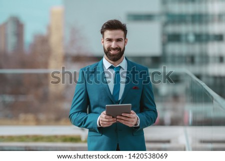 Handsome young smiling Caucasian businessman in blue suit standing on the rooftop and holding tablet. #1420538069
