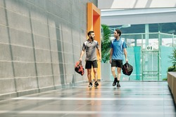 Handsome young sportsmen with gym bags walking along health club corridor and discussing news