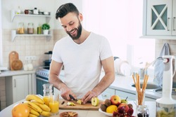 Handsome young sporty smiling man in the kitchen is preparing vegan healthy fruits salad and smoothie in a good mood