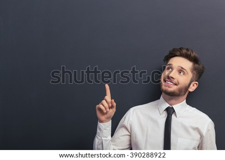 Handsome young student in white classic shirt is smiling, looking and pointing up, standing against blackboard