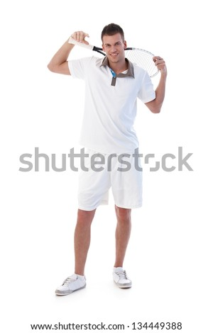Handsome young tennis player posing with tennis racket in hand, smiling.
