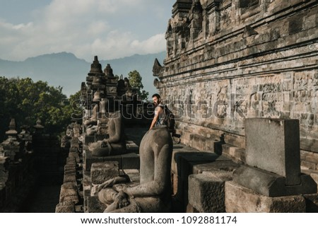 Handsome young tourist feeling the peace of the great Borobudur temple, historical famous place in the java island Indonesia. Lifestyle and travel photography. #1092881174