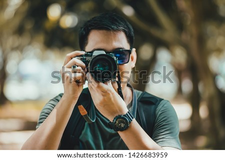 Handsome young tourists are enjoying photography. To record his travel experience