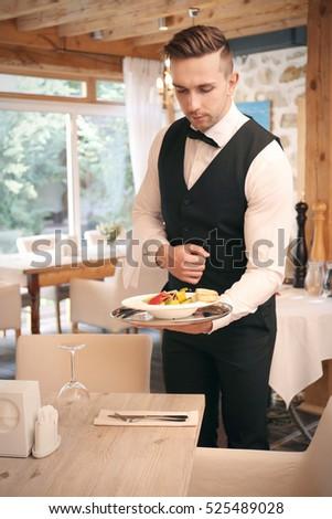 Handsome young waiter serving meals at restaurant #525489028