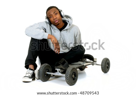Handsome youngster, black African American teenager with mountain-board and headset, hip hop urban culture.  Studio white background
