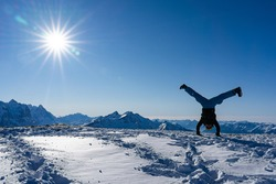 Handstand straddle on snow caped mountain peak with blue sky and bright sunbeams.
