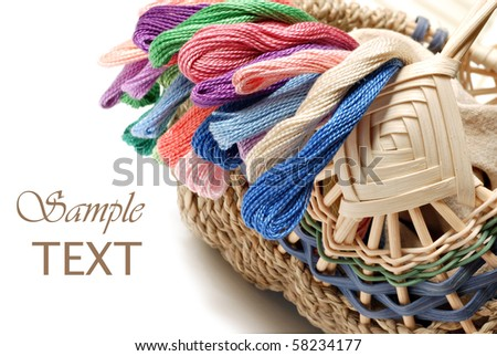 Handwoven basket with colorful skeins of thread on white background with copy space.  Macro with shallow dof.