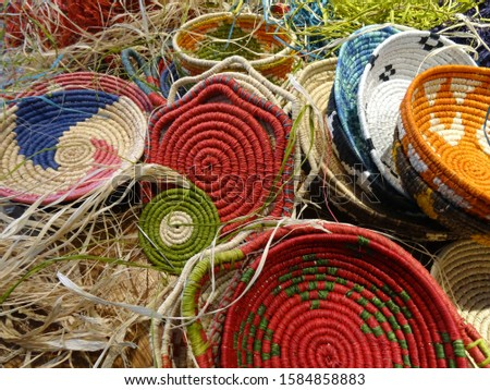 Handwoven colorful raffia baskets and its making process with a needle.                                 Photo stock ©