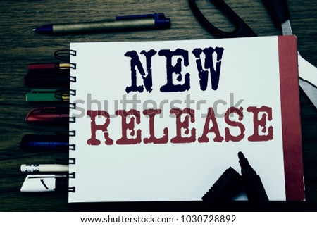 Handwriting Announcement text showing New Release . Business concept for Technology Software Update Written on notebook, wooden background with office equipment like pens scissors colourful marker