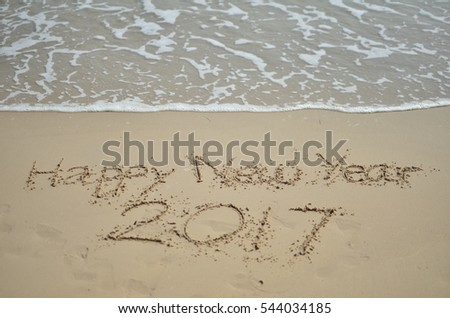 handwriting message for celebrate happy new year 2017 on the sand