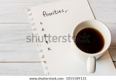 Handwriting priorities on white paper note with a cup of espresso coffee.