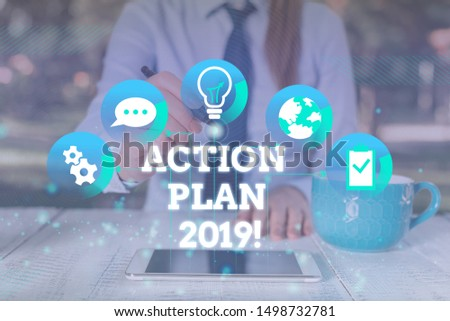 Handwriting text Action Plan 2019. Concept meaning proposed strategy or course of actions for current year Female human wear formal work suit presenting presentation use smart device.
