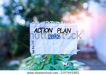 Handwriting text Action Plan 2019. Concept meaning proposed strategy or course of actions for current year Plain empty paper attached to a stick and placed in the green leafy plants.