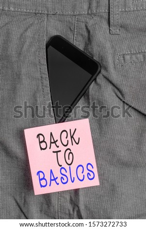 Handwriting text Back To Basics. Concept meaning Return simple things Fundamental Essential Primary basis Smartphone device inside formal work trousers front pocket near note paper.